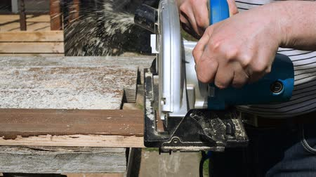 velo : Handyman using handheld saw machine outdoors.
