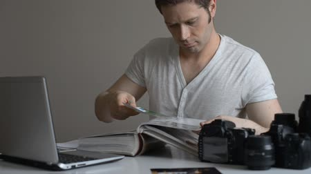 editorial : Male photographer watching photo album at his workplace. Stock Footage