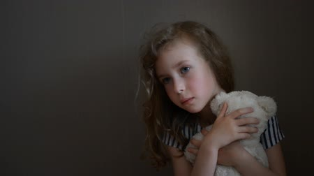 výraz : Sad little girl with bear near the wall.