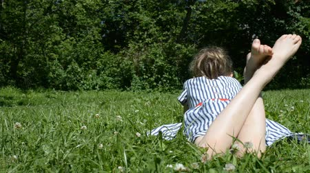 çim : Little girl lying on green grass in the park.