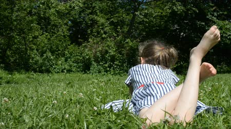 yatarken : Little girl lying on green grass in the park.
