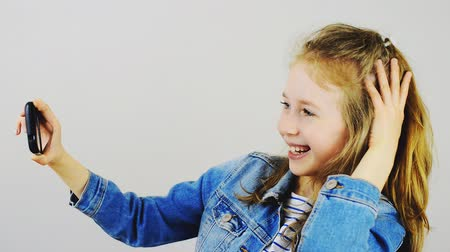obrázky : Happy little girl taking selfie with mobile phone. Dostupné videozáznamy