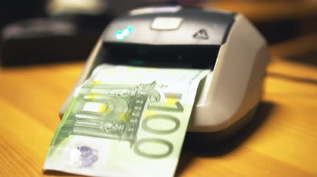 forgery : Woman using automatic counterfeit money detector. Checking 20, 50 and 100 euros.