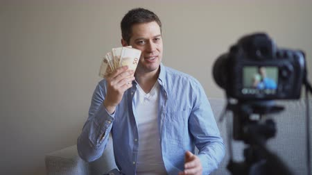 videocamera : Handsome man making video blog about money earning. Stock Footage
