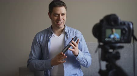 videocamera : Handsome man making video blog about tablet pc.