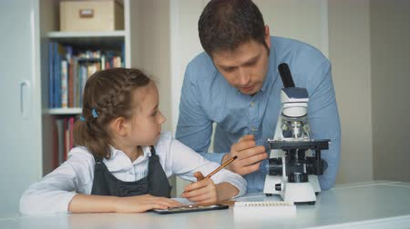 magnifier : Little girl with teacher in science class with microscope on the table.