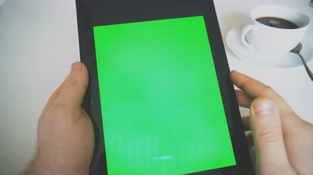 görgetés : Hand holding tablet pc with green screen. Chroma key.