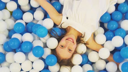 toy : Cute little girl lying in plastic balls in playroom. Stock Footage