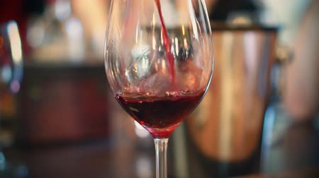 хрупкий : Pouring red wine from bottle into glass. Wine degustation.
