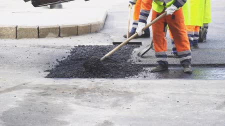 paving : Men lay asphalt on the road. Road re-construction. Stock Footage