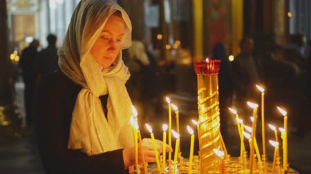 felvilágosodás : Woman lights the candle in russian orthodox church.