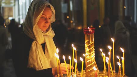 esteem : Woman lights the candle in russian orthodox church.