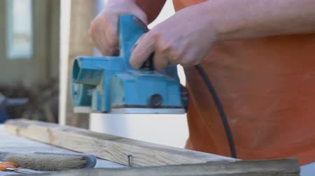 lumber : Handyman using electric wood planer outdoors.