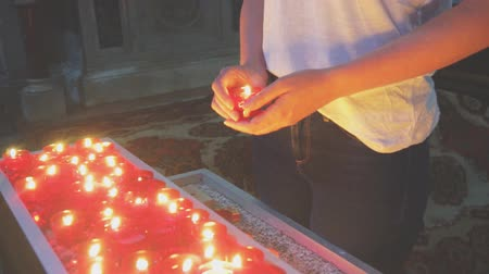 redemption : Woman holding candle near altar in church.