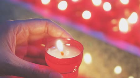 believer : Woman lights a candle near altar in church.