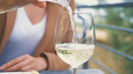 アルコール依存症 : Woman pouring glass of white wine. Vacation concept.