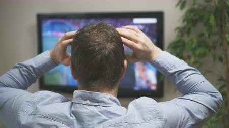 frustrado : Sad man watching a football match at home. Vídeos