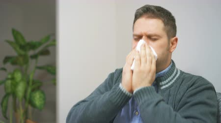 epidemy : Handsome unshaved man blowing nose to napkin.