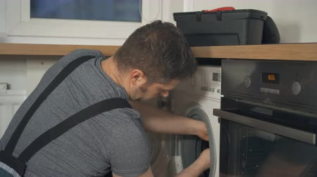 toolbox : Professional handyman in overalls repairing washing machine in the kitchen. Stock Footage