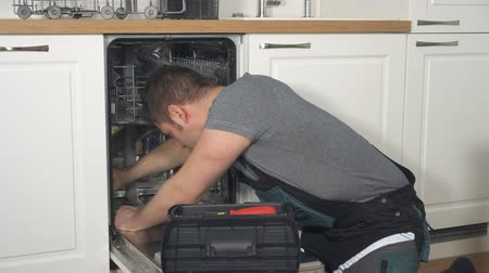 ajoelhado : Professional handyman in overalls repairing domestic dishwasher in the kitchen. Vídeos