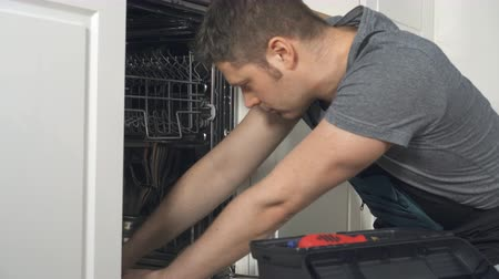 гарантия : Professional handyman in overalls repairing domestic dishwasher in the kitchen. Стоковые видеозаписи