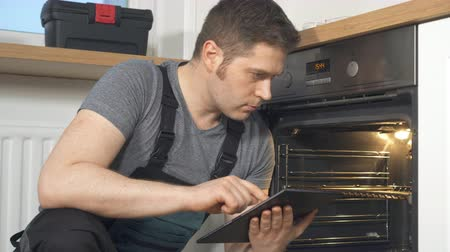 гарантия : Handyman doing inspection of domestic oven in the kitchen.