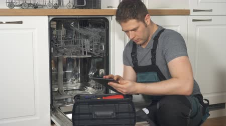 podložka : Handyman with tablet pc repairing domestic dishwasher in the kitchen.