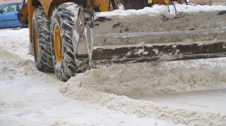 муниципальный : Tractor shoveling snow on the street. Slow-motion. Стоковые видеозаписи
