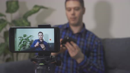 videocamera : Man making video blog about external hard drive. Stock Footage