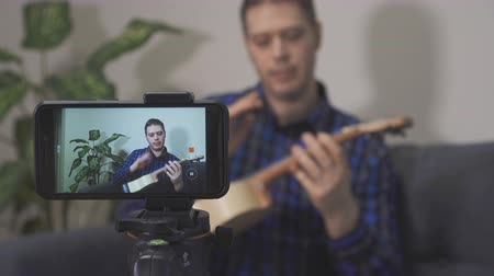 vlogging : Handsome man making video blog about musical instruments.