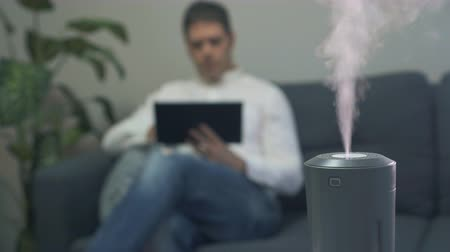 очиститель : Air humidifier at living room. Man using tablet pc on the background.