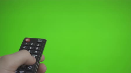 presleme : Male TV remote pressing channels over green screen. Place for your advertisement.