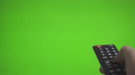 infrared : Male TV remote pressing channels over green screen. Place for your advertisement.