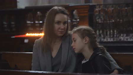 Woman and her daughter are sitting on a bench in the church.
