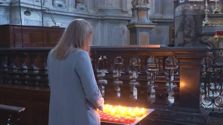 symbolismus : Woman holding candle near altar in church.
