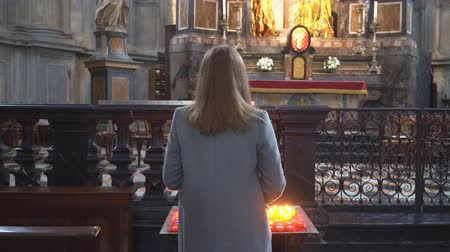 солидарность : Woman holding candle near altar in church.