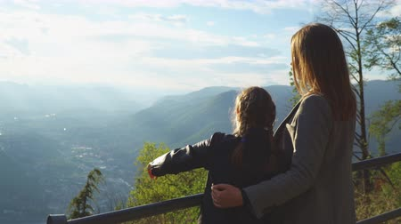 Woman and her daughter enjoying sunrise from top of mountain. Stock Footage