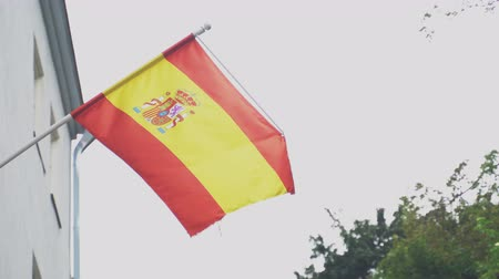 união europeia : Spanish flag on a flagpole waving on house.