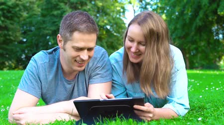 ebook : Couple lying in the park and using tablet pc.