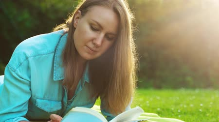 книгу : Woman lies on the grass and reads a book.