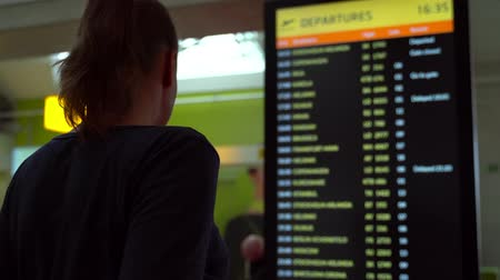 horário : Woman in front of flight information board, checking her flight.