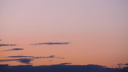 holdfény : The new moon rises among the clouds in the morning pink sky timelapse