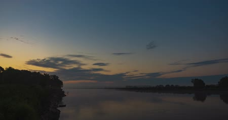 nocturnal : The timelapse of floating clouds before dawn over the river in the morning sky. Fog before dawn