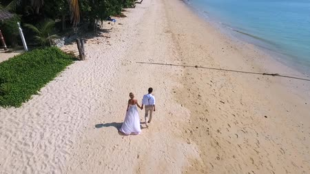 drone : Young Wedding Couple Walking on the Paradise Beach. HD aerial view. Phuket, Thailand.