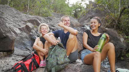 dospělý : Group of Young Tourists Laughing and Resting at the Cascade Waterfall. HD Slowmotion. Thailand.