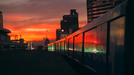 approaching subway : Beautiful Golden Sunset in Bangkok City with BTS Metro Subway Train Leaving from the Station Siam. 4K. Bangkok, Thailand - 12 NOV 2017.