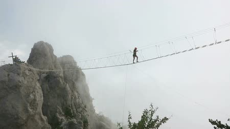 mosty : Woman crossing the chasm on the rope bridge