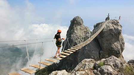 peak : Woman walking on the rope bridge over the abyss Stock Footage