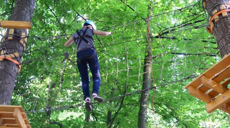difficults : The girl the teenager overcomes the obstacles between trees at height. Rope town.