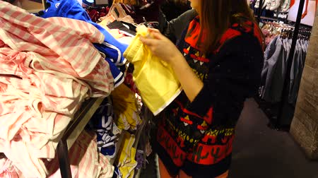associados : Shopping in outlets Europe. The girl chooses clothes. Sale and discounts.